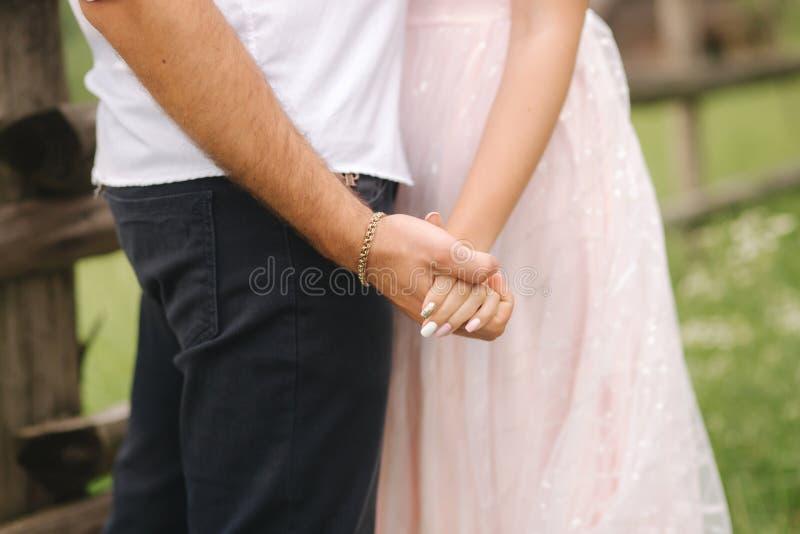 Stäng sig upp av brudgumhållbrudens händer par som att gifta sig bara arkivbilder