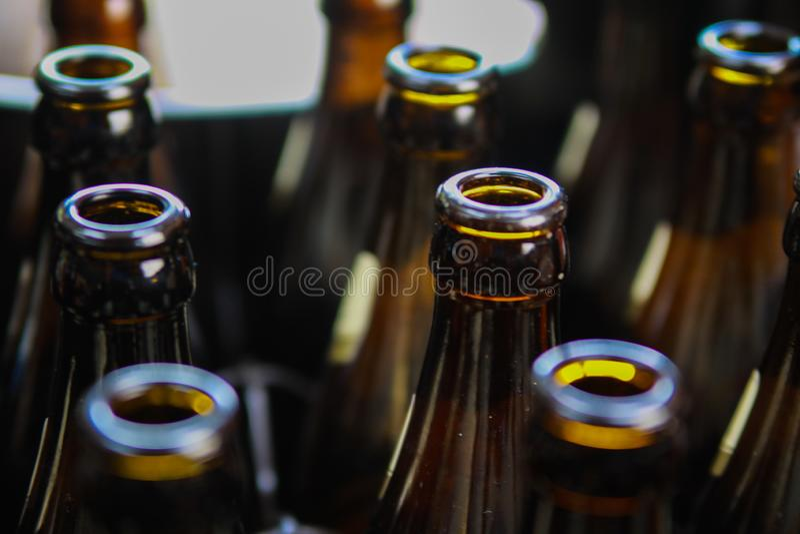 Stäng sig upp av bruna tomma ölflaskor i ett fall arkivfoton