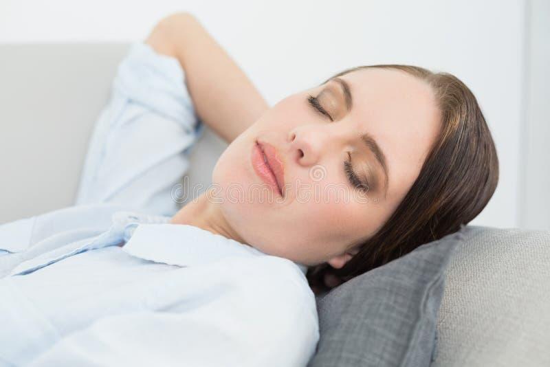Stäng sig upp av brunnen klädd härlig kvinna som sover på soffan arkivbilder