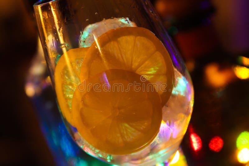 Stäng sig upp av coctailen med skivor av citron- och iskuber arkivfoton
