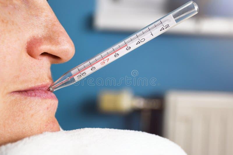 Stäng sig upp av dåligt kvinnan med influensa och termometern i hennes mun som mäter kroppstemperatur nående 39 arkivbilder