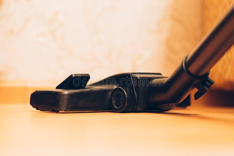 Stäng sig upp av dammsugare eller dammsugare på golv hemma, hushållsarbete och lokalvård royaltyfri bild