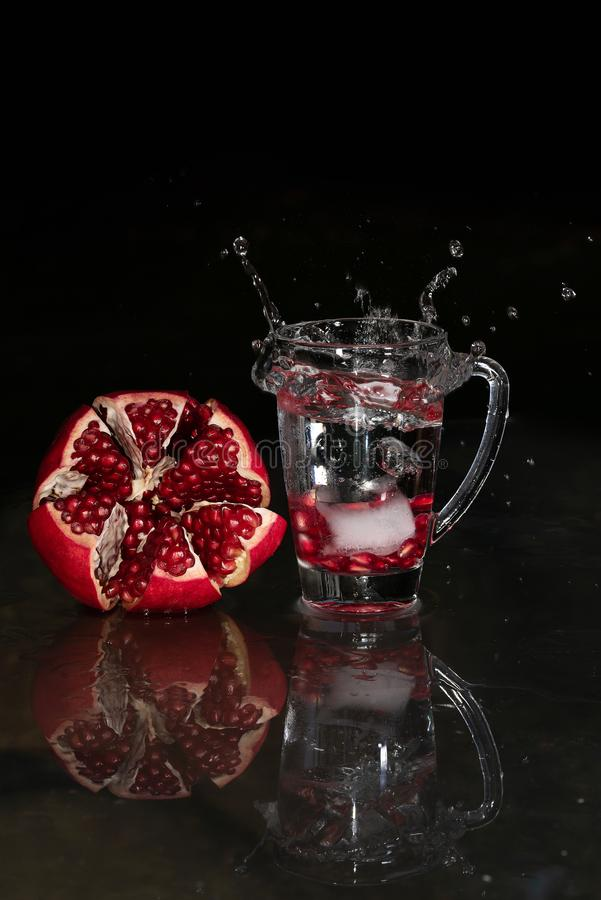 Stäng sig upp av den öppnade granatäpplet bredvid vattenexponeringsglas med frö och färgstänk royaltyfri bild