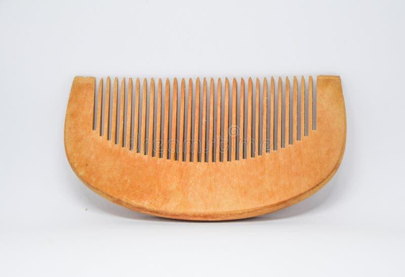 Stäng sig upp av den bruna hårkammen som göras från trä på vit bakgrund, hårkammen för att borsta hår för att vara härlig abd som royaltyfri bild
