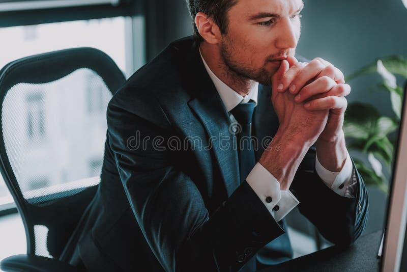 Stäng sig upp av den eleganta mannen som sätter hakan på händerna, medan tänka royaltyfri bild