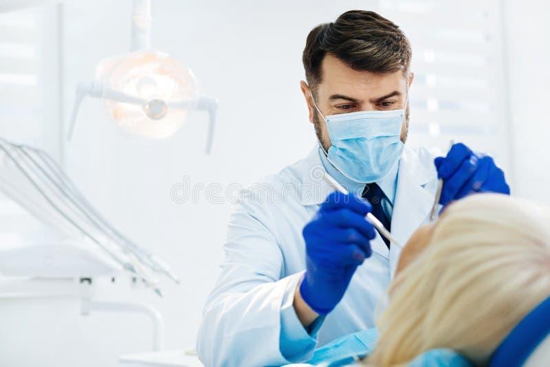Stäng sig upp av den erfarna stomatologisten som kurerar hans patient fotografering för bildbyråer