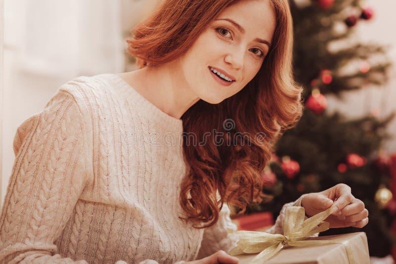 Stäng sig upp av den glade kvinnan som packar upp hennes gåva royaltyfria foton