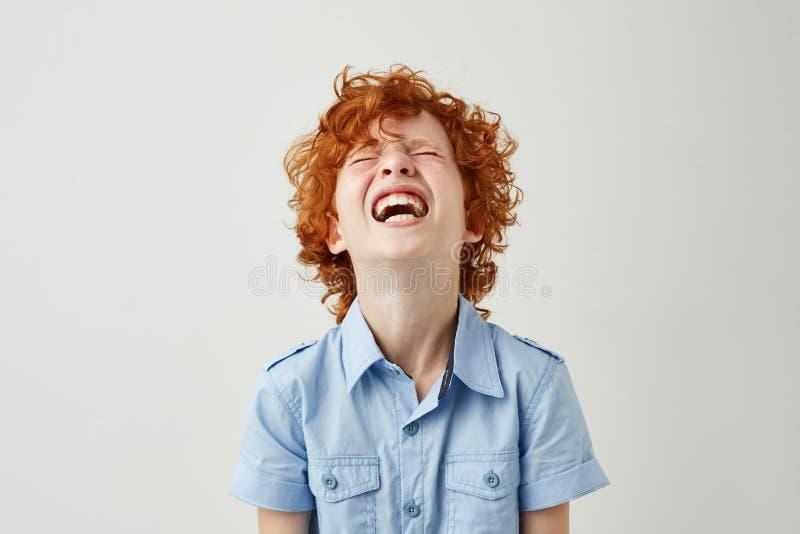 Stäng sig upp av den glade lilla ungen med ljust rödbrun lockigt hår och fräknar i blå skjorta som skrattar hållande ögonen på hå royaltyfri foto