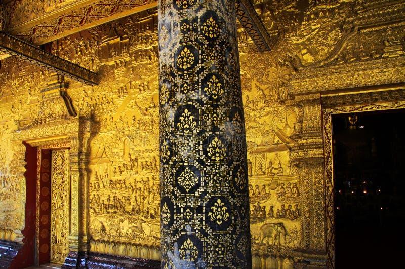 Stäng sig upp av den guld- smyckade tempelväggen - Wat Xieng Thong, Luang Prabang arkivbilder