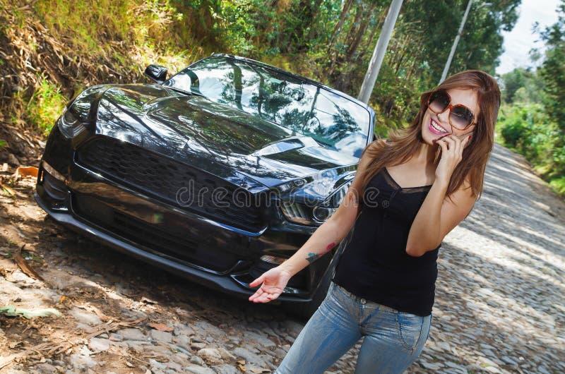 Stäng sig upp av den härliga caucasian kvinnan som använder hennes mobiltelefon och bär sunglases, svart t-skjorta och jeans och  arkivfoton
