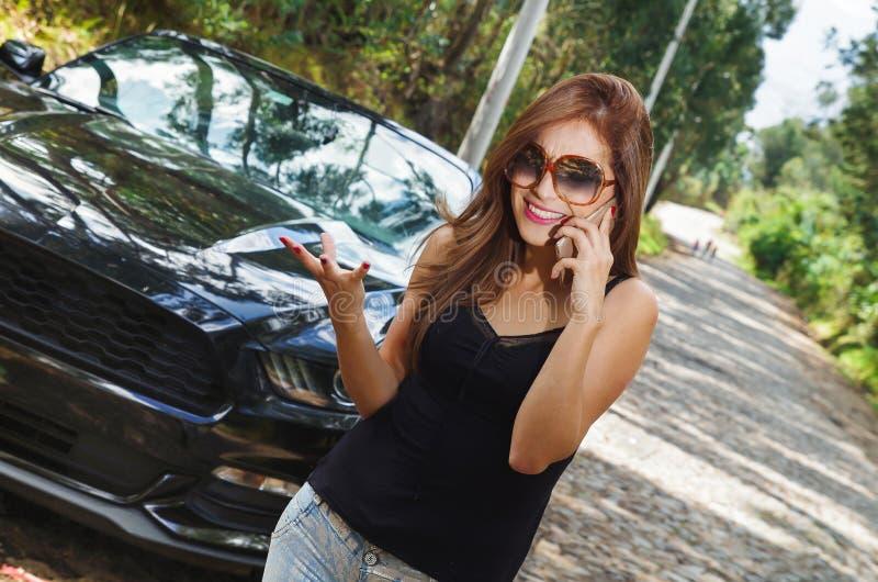 Stäng sig upp av den härliga caucasian kvinnan som använder hennes mobiltelefon och bär sunglases, svart t-skjorta och jeans och  royaltyfri fotografi