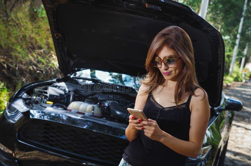 Stäng sig upp av den härliga caucasian kvinnan som använder hennes mobiltelefon och bär sunglases, svart t-skjorta och jeans och  fotografering för bildbyråer