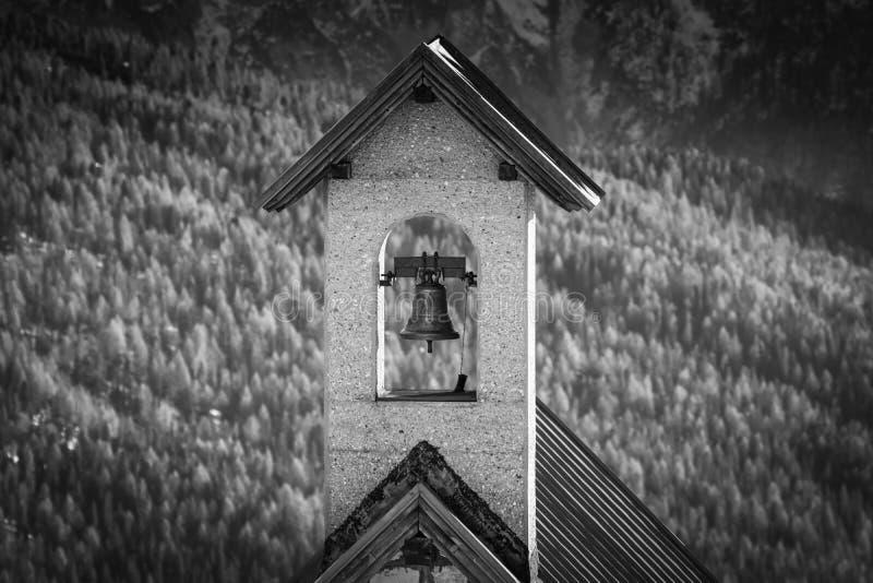 Stäng sig upp av den härliga gamla campanilen, kapelltornklockan i svartvitt i dolomites, Italien arkivfoton