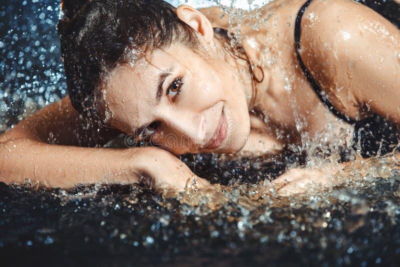 Stäng sig upp av den härliga unga kvinnan som ligger i vattnet arkivfoto