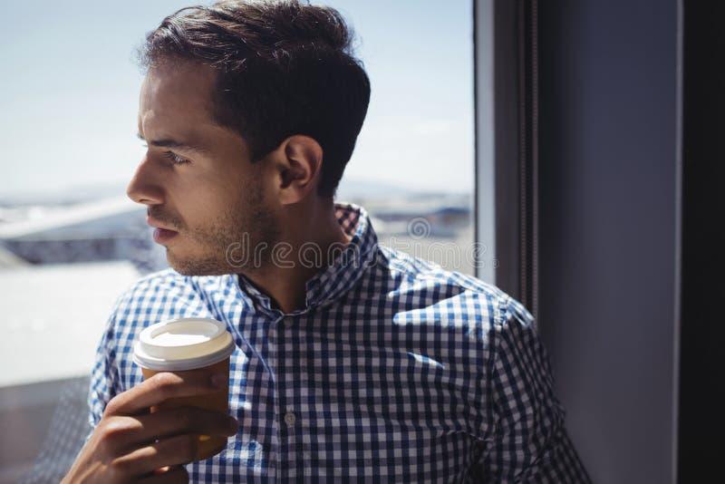 Stäng sig upp av den hållande kaffekoppen för den fundersamma affärsmannen i regeringsställning arkivbilder