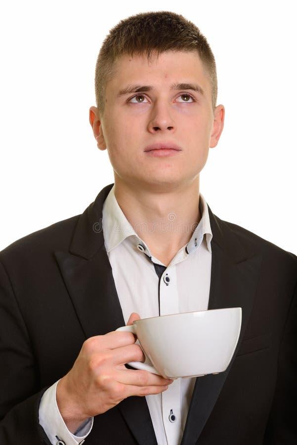 Stäng sig upp av den hållande kaffekoppen för den unga affärsmannen, medan tänka arkivfoton