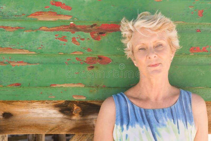 Stäng sig upp av den höga kvinnan som ser bort, medan stå mot väggen royaltyfria bilder
