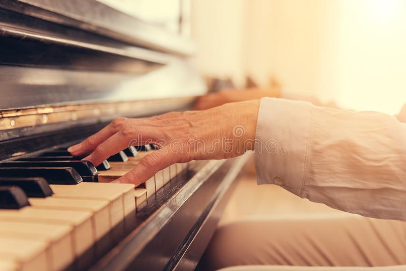 Stäng sig upp av den höga kvinnan som spelar pianot arkivbilder