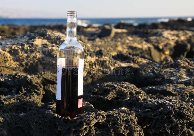 Stäng sig upp av den halvfulla rött vinflaskan vaggar på av stranden med bakgrund för havvågor - El Cotillo, Fuerteventura royaltyfri foto