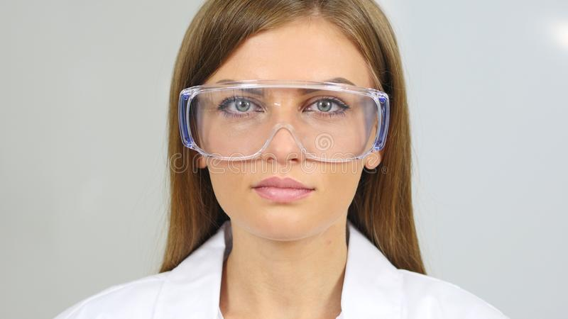 Stäng sig upp av den kvinnliga reseachforskaren, doktorn som bär skyddande exponeringsglas fotografering för bildbyråer