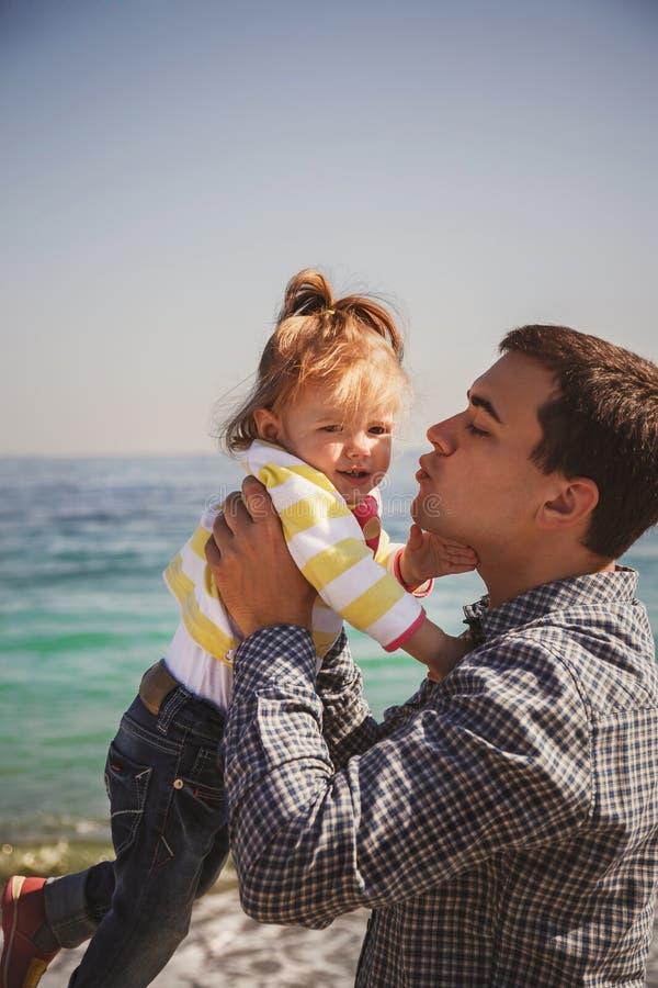 Stäng sig upp av den lyckliga älska familjen, fader, och den lilla dottern tillsammans nära havet, barnfader rymmer hans unge i a royaltyfria foton