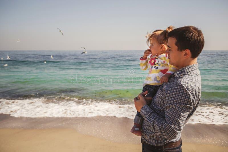Stäng sig upp av den lyckliga älska familjen, fader, och den lilla dottern tillsammans nära havet, barnfader rymmer hans unge i a royaltyfria bilder