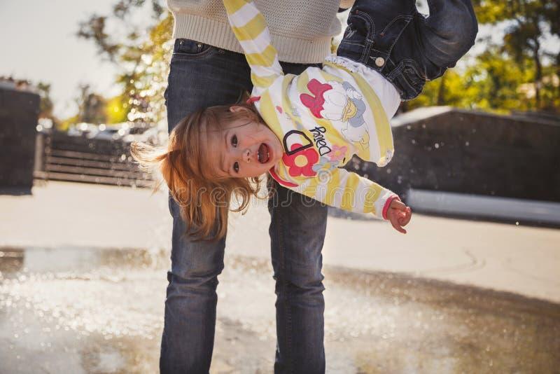 Stäng sig upp av den lyckliga gladlynta älska familjen, barn som modern är den uppochnervända hållande lilla flickan royaltyfri bild