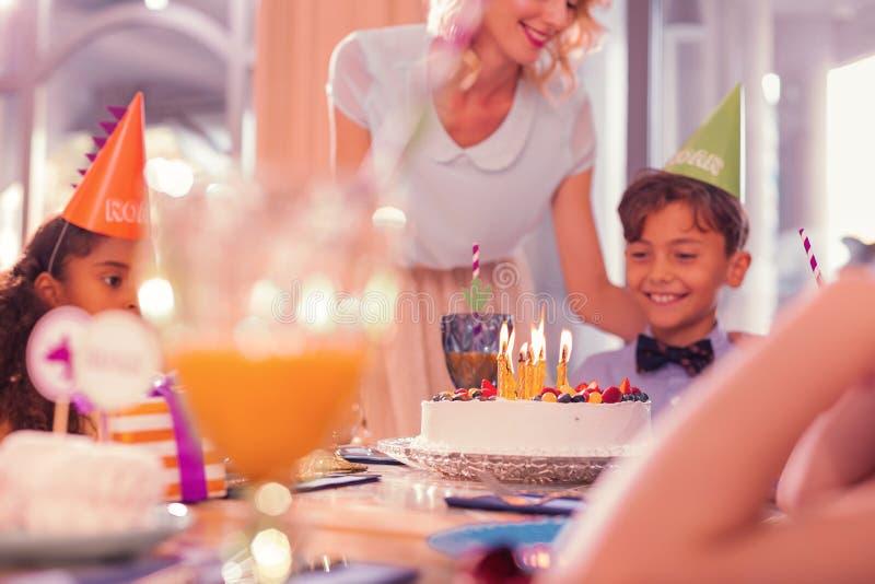 Stäng sig upp av den lyckliga pojken som ser stearinljusen på kakan royaltyfri fotografi