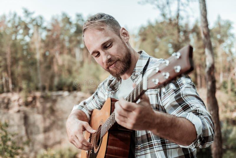 Stäng sig upp av den lyckliga stiliga skäggiga mannen som spelar sitta för gitarr som är fjällnära royaltyfri bild