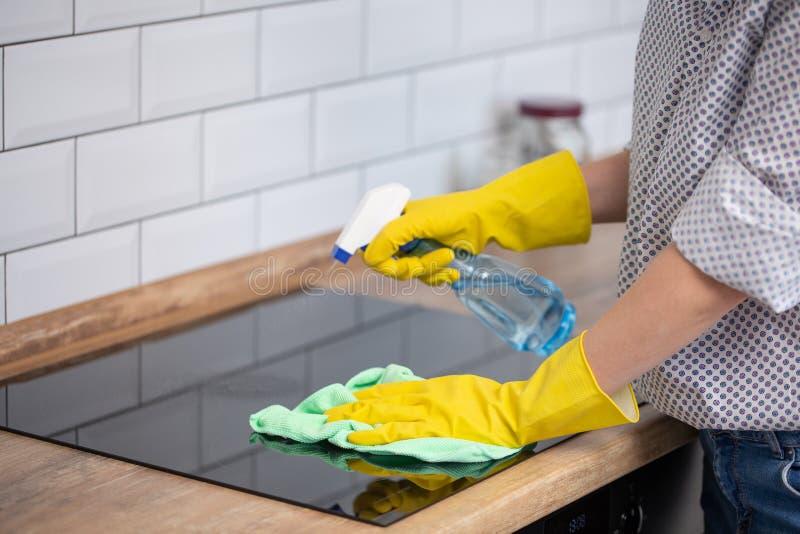 Stäng sig upp av den mänskliga handen med skyddande handskar som gör ren induktionshoben med trasan och rymmer sprejflaskan royaltyfri foto