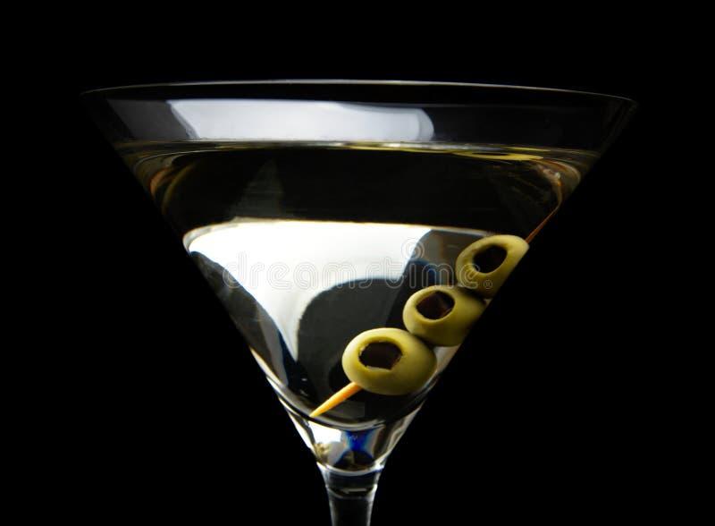 Stäng sig upp av den Martini coctailen med oliv som isoleras på svart arkivfoto