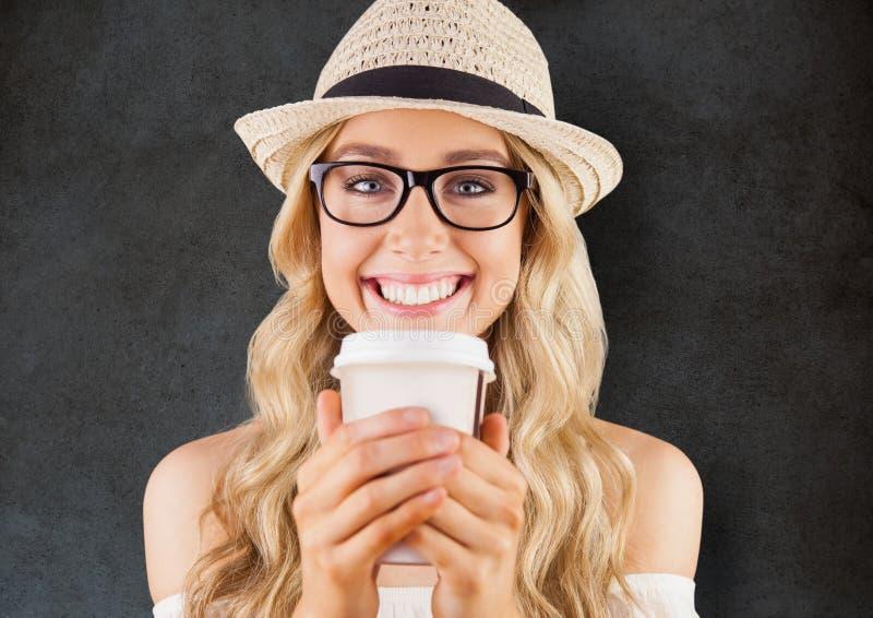 Stäng sig upp av den millennial kvinnan som ler med kaffe mot den gråa grungeväggen arkivfoto