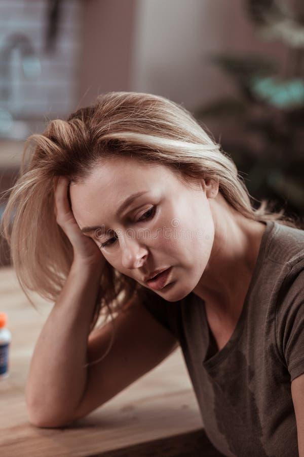 Stäng sig upp av den mogna blonda kvinnan som känner sig stressad och sjuk royaltyfri fotografi