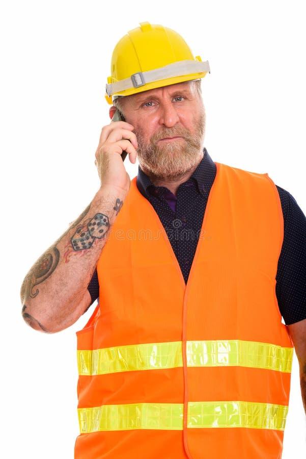 Stäng sig upp av den mogna skäggiga manbyggnadsarbetaren som talar på telefonen arkivfoton