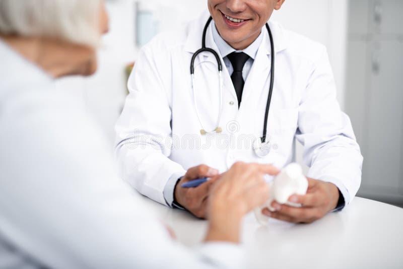 Stäng sig upp av den positiva doktorn som ler till hans patient arkivbilder