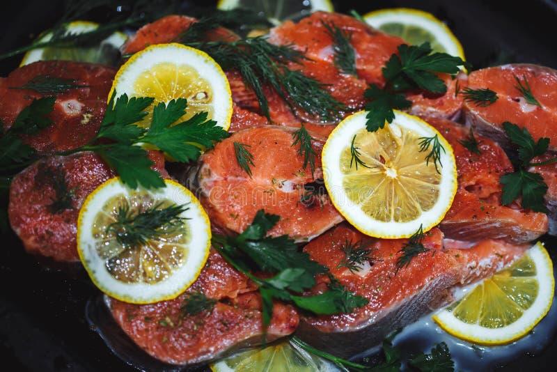 Stäng sig upp av den röda fisken som skivas med skivor av citronen och dill En läcker maträtt arkivfoto