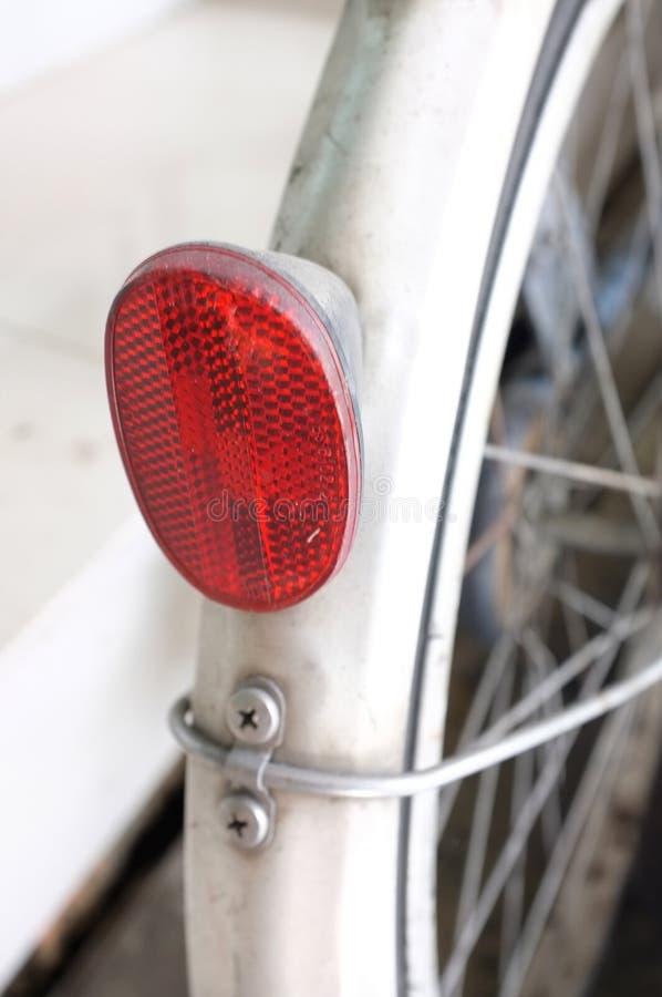 Stäng sig upp av den röda glass reflektordelen av cykeln royaltyfri foto