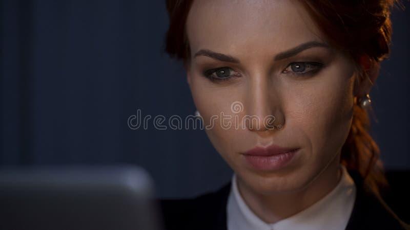 Stäng sig upp av den säkra affärskvinnan som ser bärbar datorskärmen i företagskontor arkivbilder
