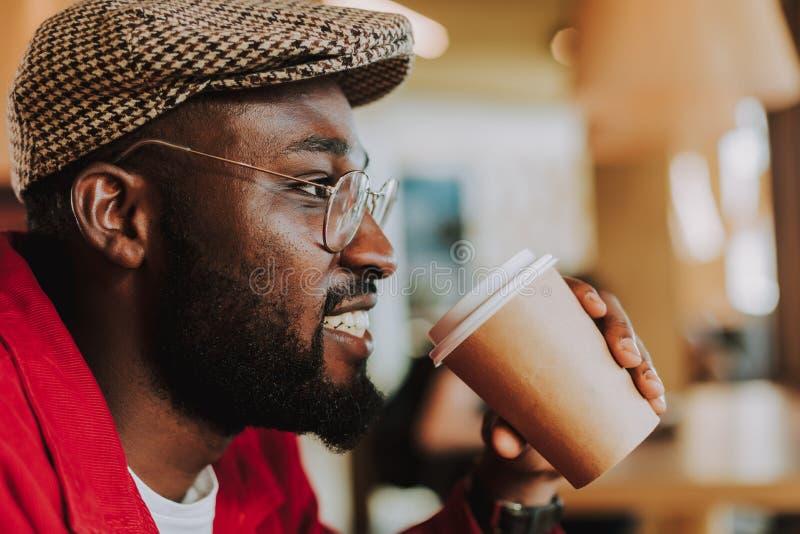 Stäng sig upp av den skäggiga mannen som ler och dricker kaffe fotografering för bildbyråer