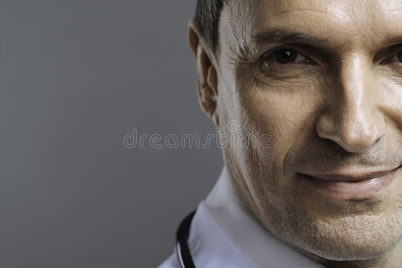 Stäng sig upp av den stiliga doktorn som ler på en grå bakgrund royaltyfri bild