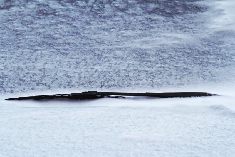 Stäng sig upp av den svarta bilvindrutatorkaren som täckas i snö fotografering för bildbyråer