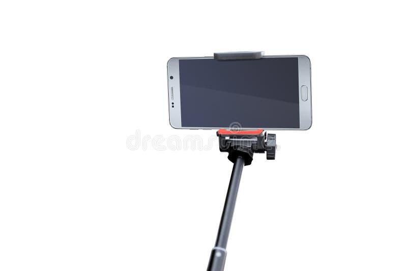 Stäng sig upp av den tomma smartphoneskärmen med den svarta selfiepinnen som isoleras på vit bakgrund royaltyfri foto