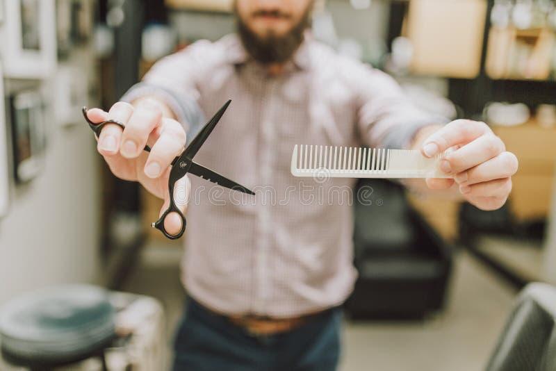 Stäng sig upp av den trendiga hårkammen och sax för hipsterfrisörinnehav royaltyfri fotografi