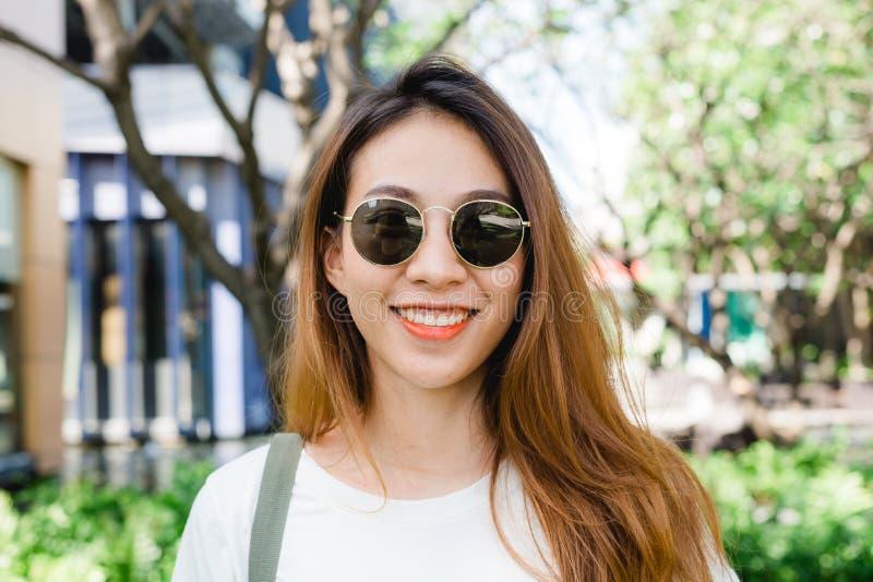 Stäng sig upp av den unga asiatiska kvinnan som ler i trädgården som tycker om hennes stadslivsstil på helgmorgon arkivbild