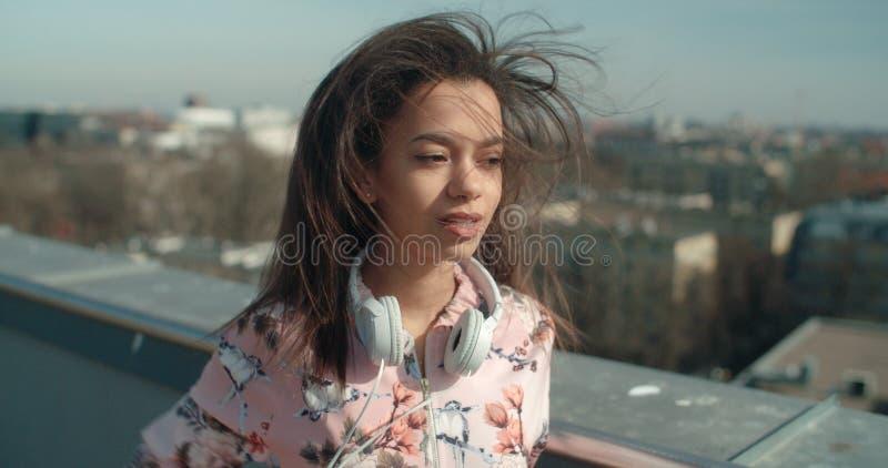 Stäng sig upp av den unga härliga kvinnan som tycker om tid på ett tak arkivbild