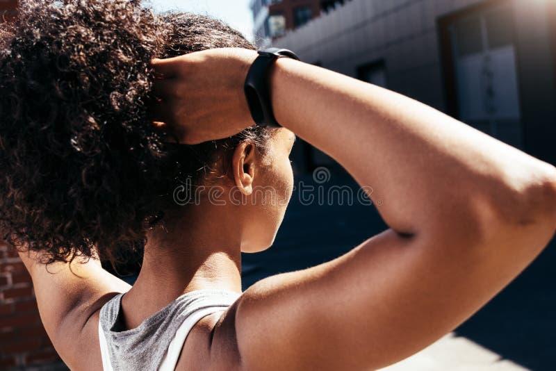 Stäng sig upp av den unga kvinnan som gör hennes hår arkivbilder