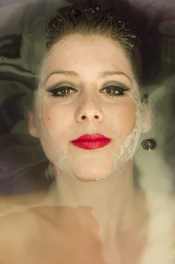 Stäng sig upp av den unga kvinnan som ligger i vattnet Koppla av makeup arkivbilder
