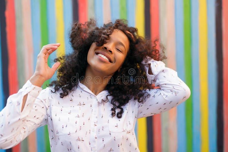 Stäng sig upp av den unga kvinnan som rymmer hennes hår fotografering för bildbyråer