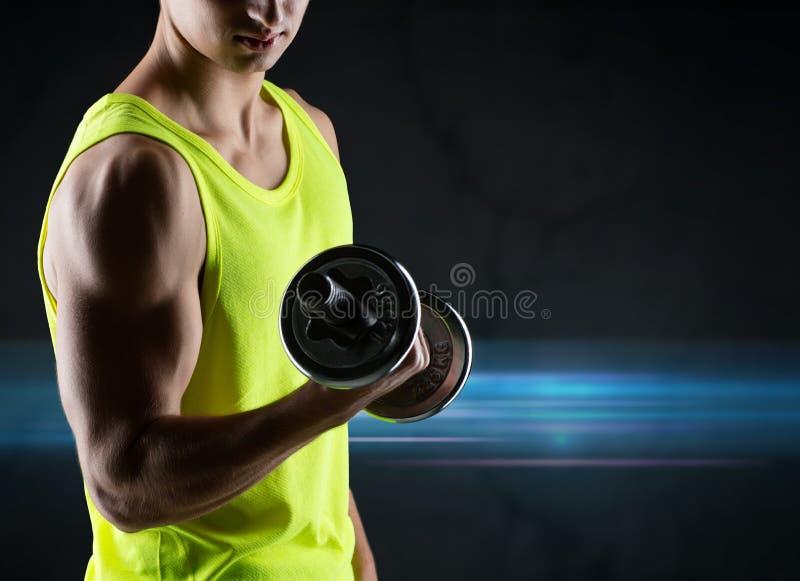 Stäng sig upp av den unga mannen med hanteln som böjer biceps royaltyfria foton
