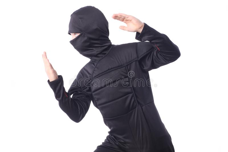Stäng sig upp av den unga pojken som bär en dräkt av ninjaen fotografering för bildbyråer